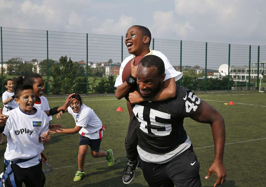 Oakland Raiders Marcel Reece plays football with children during an event in September 2014.  Photo: Lefteris Pitarakis, Associated Press