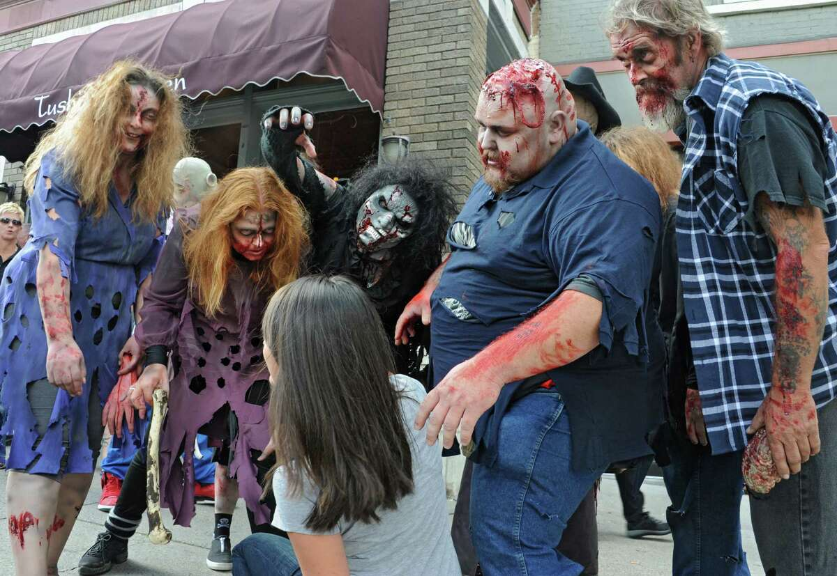 Zombies from the Double M haunted hayride scare Jennifer Schaffino of El Paso, TX as they roam around Broadway on Tuesday, Sept. 23, 2014 in Saratoga Springs, N.Y. (Lori Van Buren / Times Union)