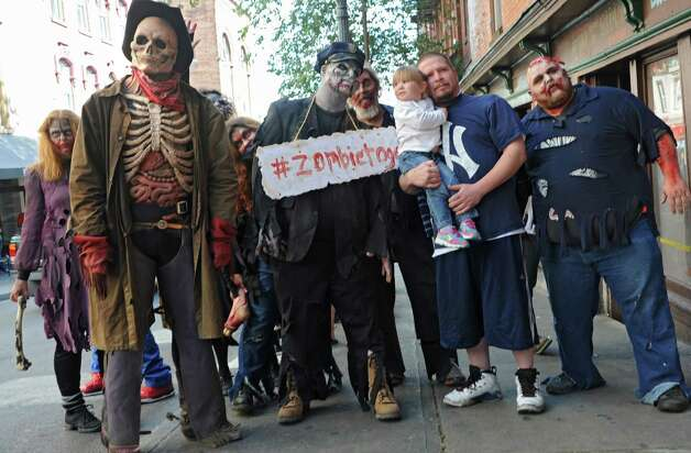 Chris Barnes of Saratoga Springs and his daughter Brooklyn, 2, get their photo taken with zombies from the Double M haunted hayride as they roam the streets on Tuesday, Sept. 23, 2014 in Saratoga Springs, N.Y. (Lori Van Buren / Times Union) Photo: Lori Van Buren