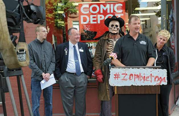 Leo Martin, co-owner of Double M, speaks as the Double M holds a press conference in front of Comic Depot at 514 Broadway on Monday, Sept. 22, 2014 in Saratoga Springs, N.Y. The Double M which holds haunted hayrides announced that on Tuesday, September 23rd at 2pm their zombies will arrive in Downtown Saratoga for #zombietoga where they will roam for approximately 1-2 hours. Standing behind Martin, from left, are Dan Barner, founder of Prolific Marketing, Pete Bardunias, president of Chamber of Southern Saratoga County, zombie Scary Harry, and Jennifer Marin, co-owner of Double M. (Lori Van Buren / Times Union) Photo: Lori Van Buren / 00028703A