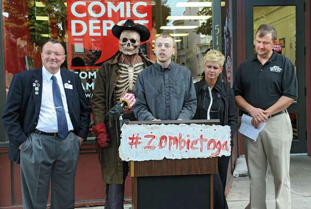 Dan Barner, founder of Prolific Marketing, speaks as the Double M holds a press conference in front of Comic Depot at 514 Broadway on Monday, Sept. 22, 2014 in Saratoga Springs, N.Y. The Double M which holds haunted hayrides announced that on Tuesday, September 23rd at 2pm their zombies will arrive in Downtown Saratoga for #zombietoga where they will roam for approximately 1-2 hours. Standing behind Barner, from left, are Pete Bardunias, president of Chamber of Southern Saratoga County, zombie Scary Harry, and Jennifer and Leo Martin, owners of Double M. (Lori Van Buren / Times Union) Photo: Lori Van Buren / 00028703A