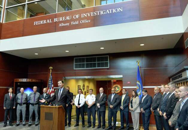 FBI Director James B. Comey, center, at podium, the presidentially appointed seventh Director of the FBI, is joined by Albany area local, state and federal law enforcement agency partners during a news conference Tuesday Sept. 23, 2014, in Albany, NY.  (John Carl D'Annibale / Times Union) Photo: John Carl D'Annibale / 00028720A