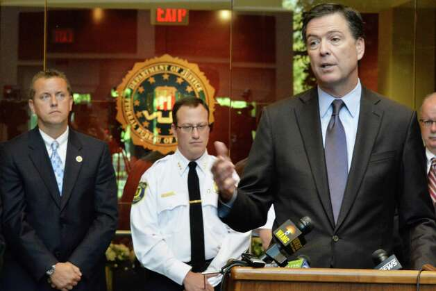 FBI Director James B. Comey, right, the presidentially appointed seventh Director of the FBI, speaks during a news conference Tuesday Sept. 23, 2014, in Albany, NY.  At left is Albany County Sheriff Craig Apple and Albany Police Chief Steve Krokoff, center. (John Carl D'Annibale / Times Union) Photo: John Carl D'Annibale / 00028720A
