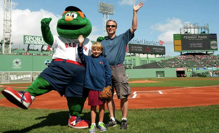 Kevin Osinski and son Cooper on the field at Fenway Park with the Boston Red Sox mascot during a ceremony where he was recognized as Blood Donor of the Game by the team and American Red Cross. Photo: Contributed Photo / Fairfield Citizen