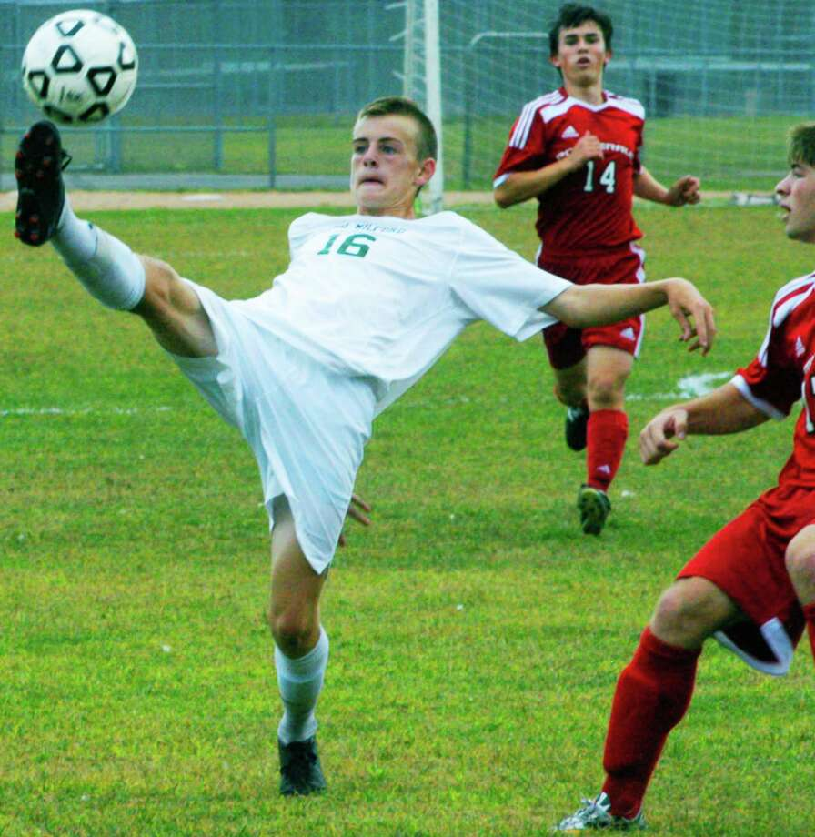 Getting their kicks  The New Milford High School boys' soccer side has built a 5-0 ledger through its early-season matches in the South-West Conference. Coach Antony Howard's Green Wave had surrendered just three goals through five matches thanks to the efforts of goalkeeper Adam Llerena and a staunch defensive corps. Above, NMHS' Jack Walsh demonstrates a fair share of agility Saturday, Sept. 20 to gain possession of the ball during a 2-1 triumph over visiting Pomperaug. For the story and more photos, as well as other high school sports coverage, see the Oct. 3 edition of The Spectrum and check updates at www.newmilfordspectrum.com. Photo: Norm Cummings / The News-Times
