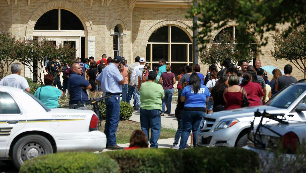 Parents line up Wednesday Sept. 24, 2014, outside Harris Middle school to pick up their children after a student brought a gun to school and it accidentally discharged. No one was hurt in the incident.