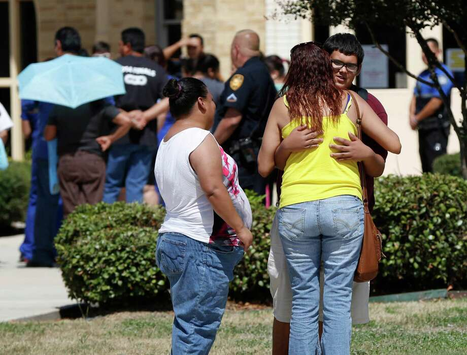Miriam Ayala hugs her nephew Jose Preciadio, Wednesday Sept. 24, 2014, outside Harris Middle school after Jose's mother, Susan Martinez picked up him u from school. Earlier in the day a student brought a gun to school and it accidentally discharged. No one was hurt in the incident. Photo: William Luther, San Antonio Express-News / © 2013 San Antonio Express-News