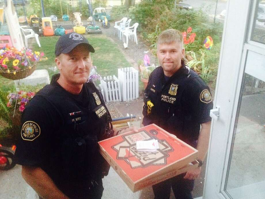 But did they get a tip?Police officers Michael Filbert (left) and Royce Curtiss protect and serve pizza at Steve Huckins' home in Portland, Ore., after a Pizza Hut driver was hurt in a crash. Huckins and his wife were surprised to see Portland's finest delivering their pizza, to say the least. Photo: Steve Huckins, Associated Press