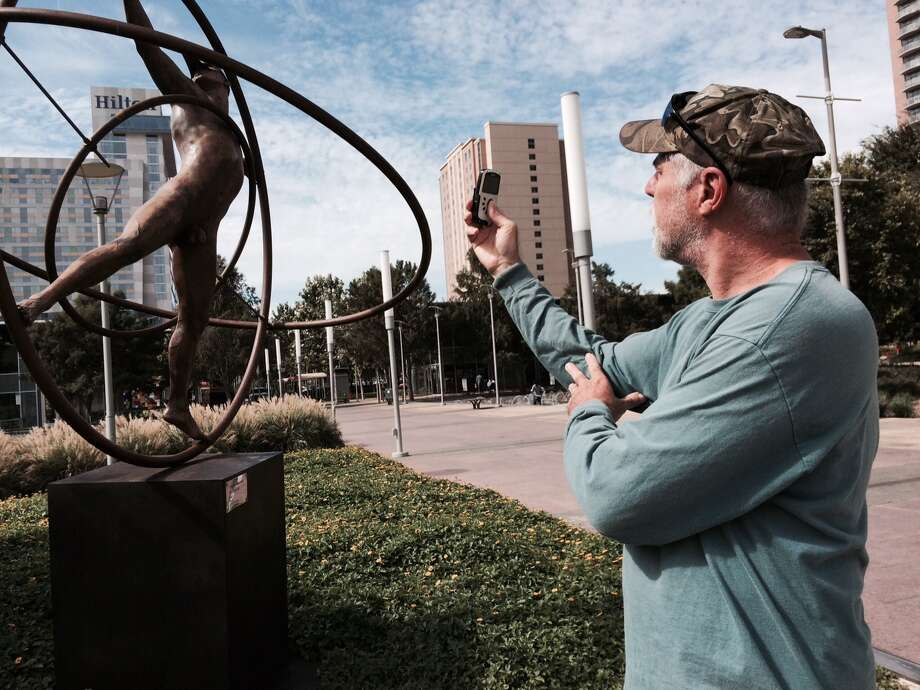 Jim Thomas of College Station takes a photo of Universal Man, a bronze sculpture at Discovery Green, Sept. 24, 2014. (Carol Christian/ Houston Chronicle)