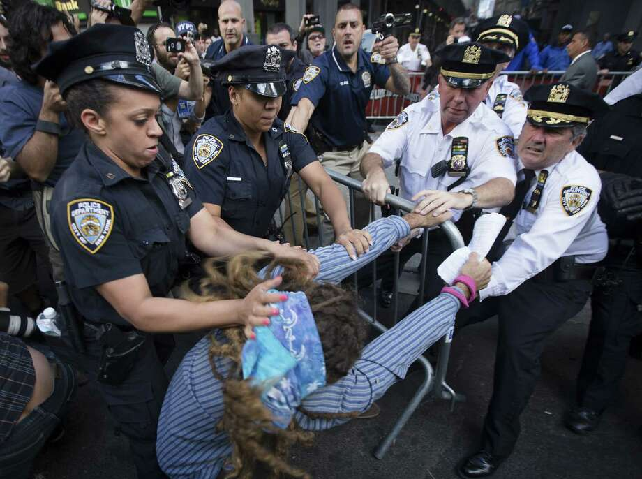 Protestors and police wrestle in New York City during a march in demanding action on climate change. A reader comments on  how the Texas Board of Education is reacting to  climate change.  Photo: John Minchillo / Associated Press / FR170537 AP