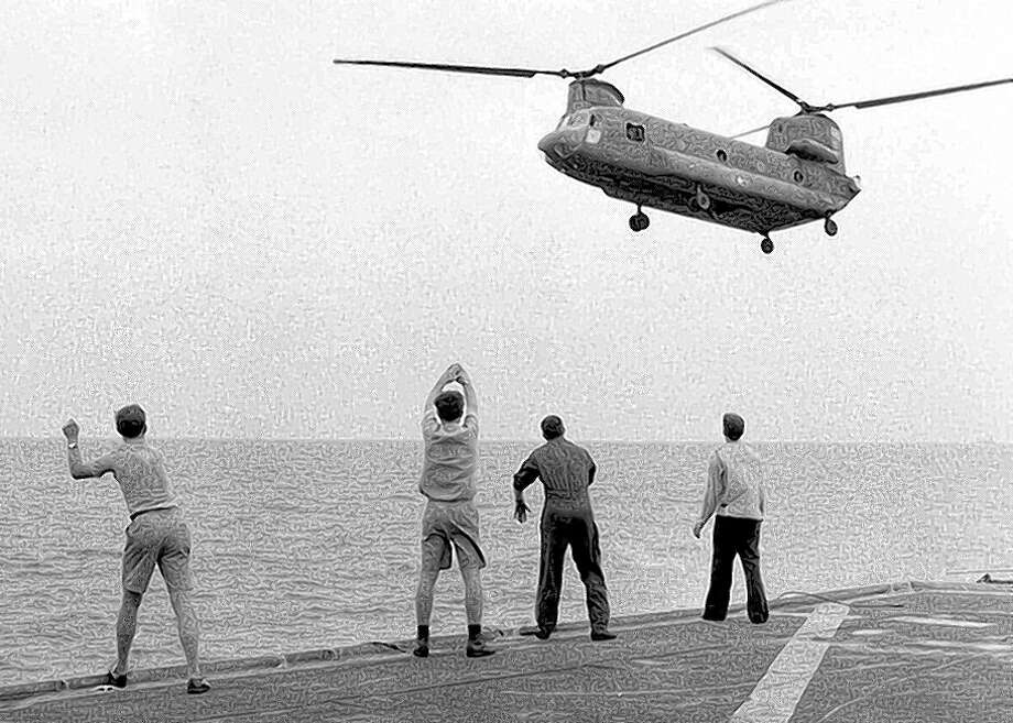 Aboard the carrier Kirk, crew members signal a Chinook pilot to hover over the deck and drop his passengers. Photo: Hugh Doyle / American Experience Films/PBS / ONLINE_YES