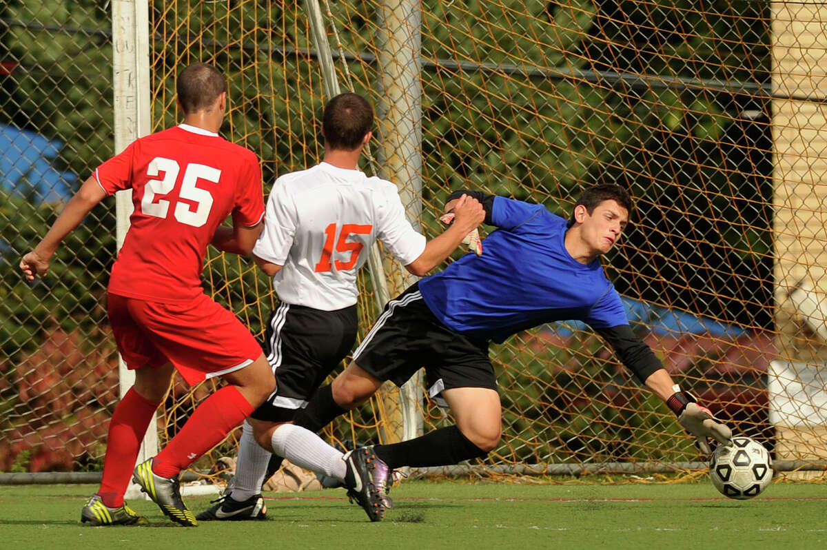 Stamford goalie Andrew Kydes dives unsuccessfully for a shot from Greenwich's Bernardo Franca while being under pressure from Stamford's Michael Nunziante during their soccer game at Stamford High School in Stamford, Conn., on Wednesday, Sept. 24, 2014. Stamford won, 4-2.
