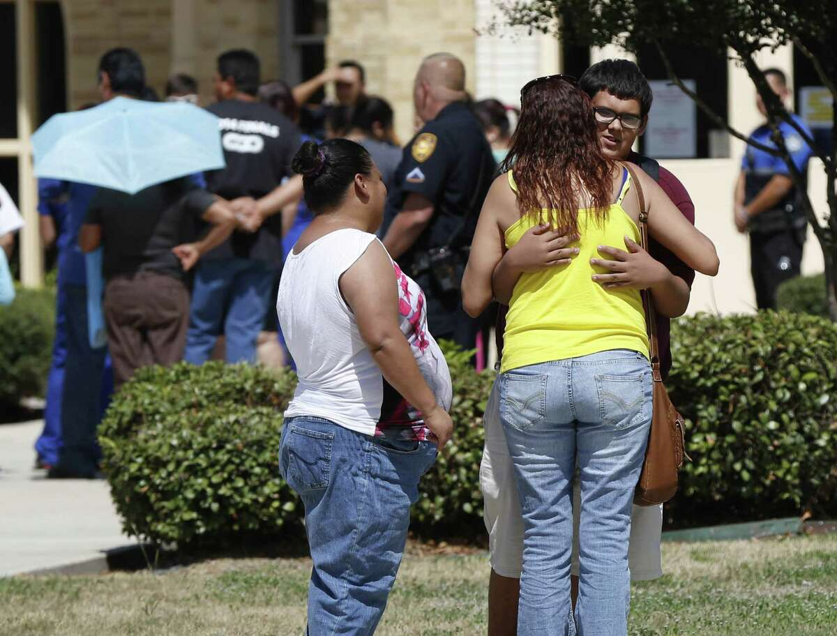 Miriam Ayala hugs nephew Jose Preciadio outside Harris Middle School after Jose's mother, Susan Martinez, came to pick him up.
