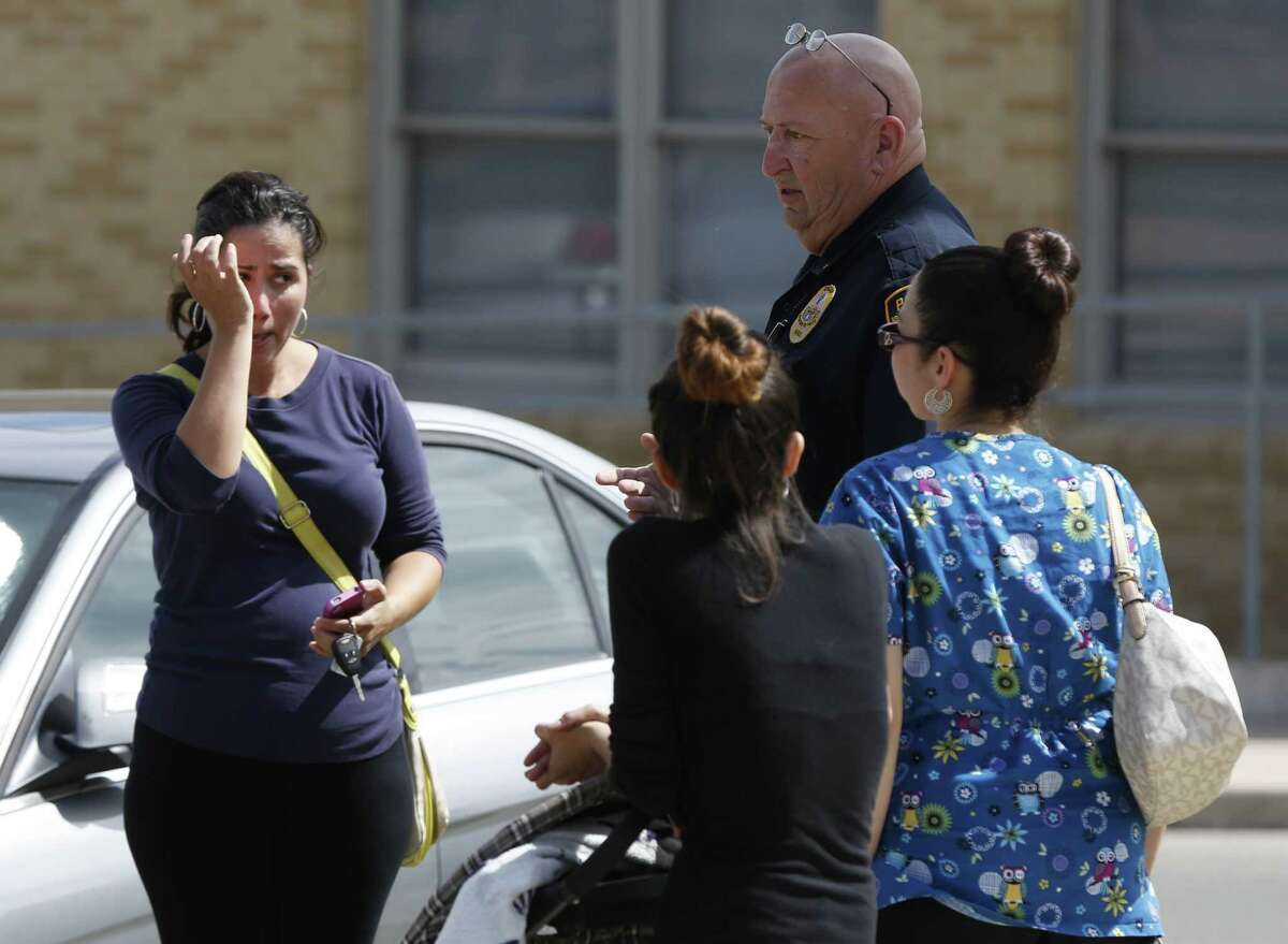 People listen to a police officer at Harris Middle School after a gun that was brought to school accidentally discharged. No one was hurt in the incident, and two students have been detained.