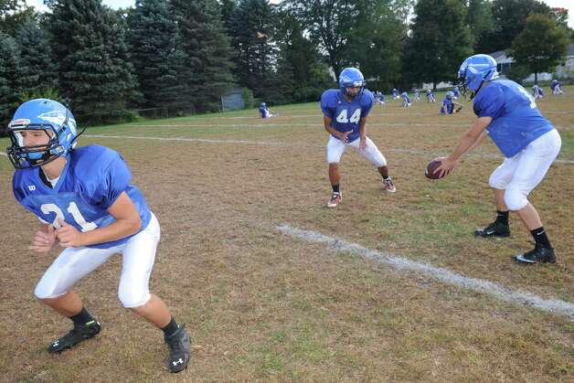 Hoosic Valley High School football running backs Tom Madigan, left, Issac Sanchez, center, and quarterback  Colin Claus during practice on Wednesday Sept. 24, 2014 in Schaghticoke, N.Y. (Michael P. Farrell/Times Union) Photo: Michael P. Farrell / 00028726A