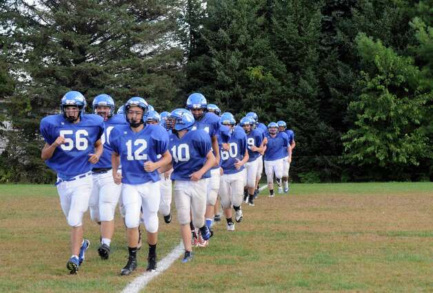 Hoosic Valley High School football quarterback Colin Claus, center #12, leads his team as they warmup during practice on Wednesday Sept. 24, 2014 in Schaghticoke, N.Y. (Michael P. Farrell/Times Union) Photo: Michael P. Farrell / 00028726A