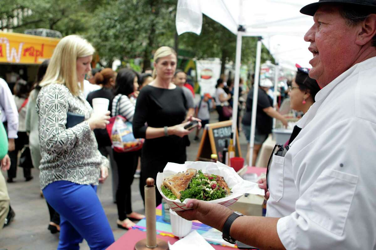 Chef Roy Rodriguez calls out customer names while serving healthy lunches during the City Hall Farmers Market on Wednesday, Sept. 24, 2014, in Houston.