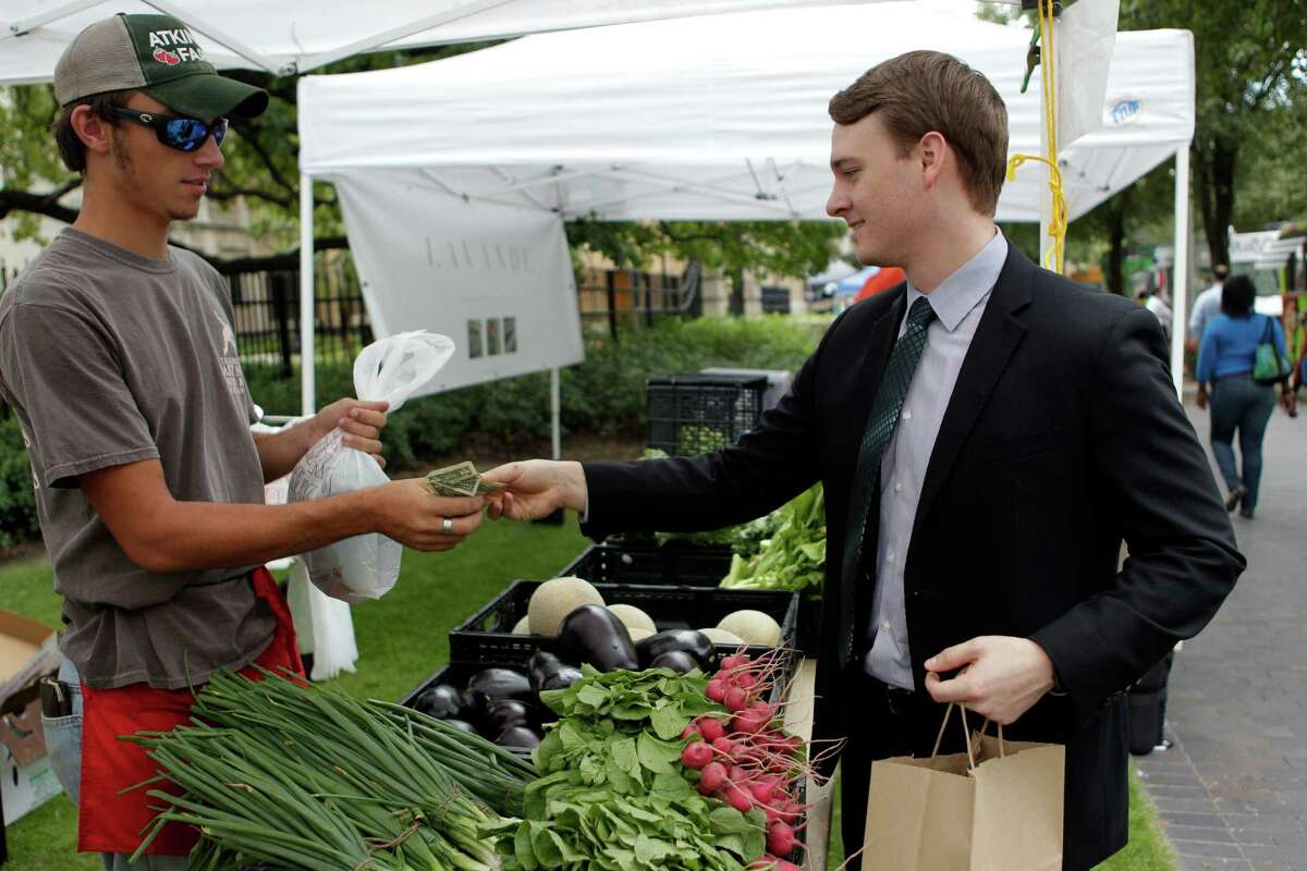 Andrew Brown purchases radishes from Adtinson Farms during the City Hall Farmers Market on Wednesday, Sept. 24, 2014, in Houston.The City Hall Farmers Market has re-opened for its 9th season, and hosted by Urban Harvest. Approximately 30 vendors, such as local farmers, pre-prepared foods, food trucks, are present from 11-1:30 p.m. every Wednesday.