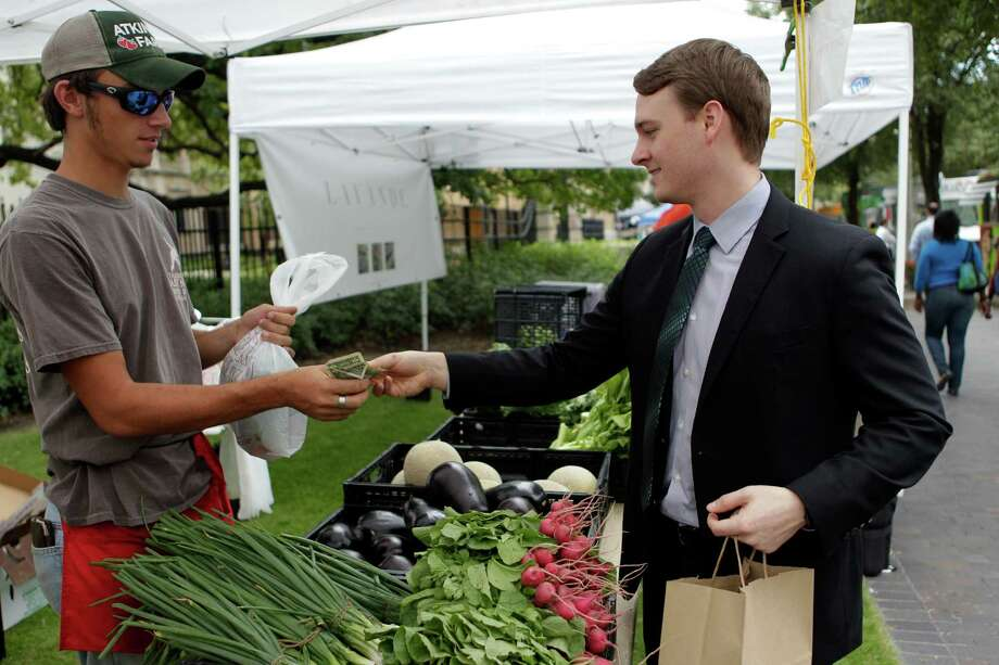 Andrew Brown purchases radishes from Adtinson Farms  during the City Hall Farmers Market on Wednesday, Sept. 24, 2014, in Houston.The City Hall Farmers Market has re-opened for its 9th season, and hosted by Urban Harvest. Approximately 30 vendors, such as local farmers, pre-prepared foods, food trucks, are present from 11-1:30 p.m. every Wednesday. Photo: Mayra Beltran, Houston Chronicle / © 2014 Houston Chronicle