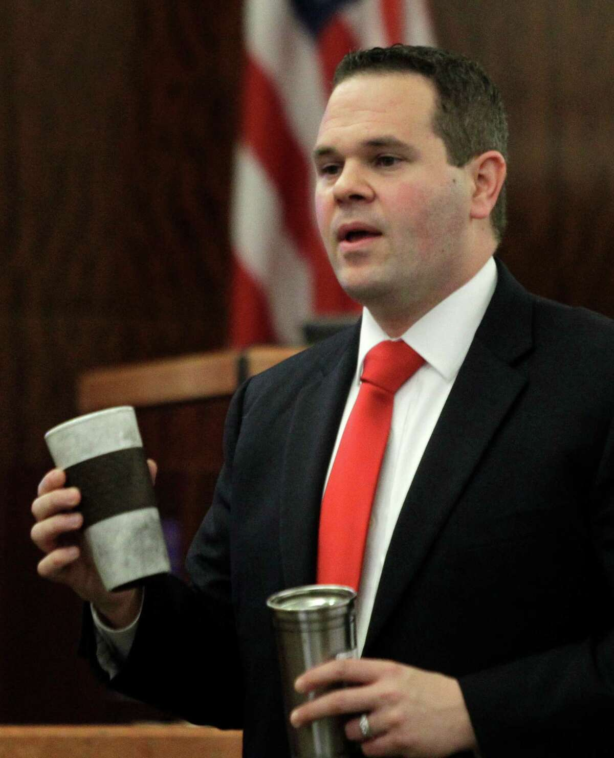 """Assistant District Attorney Justin Keiter holds up two coffee mugs during his closing arguments Wednesday. He said the defendant's guilt was """"in the details."""""""