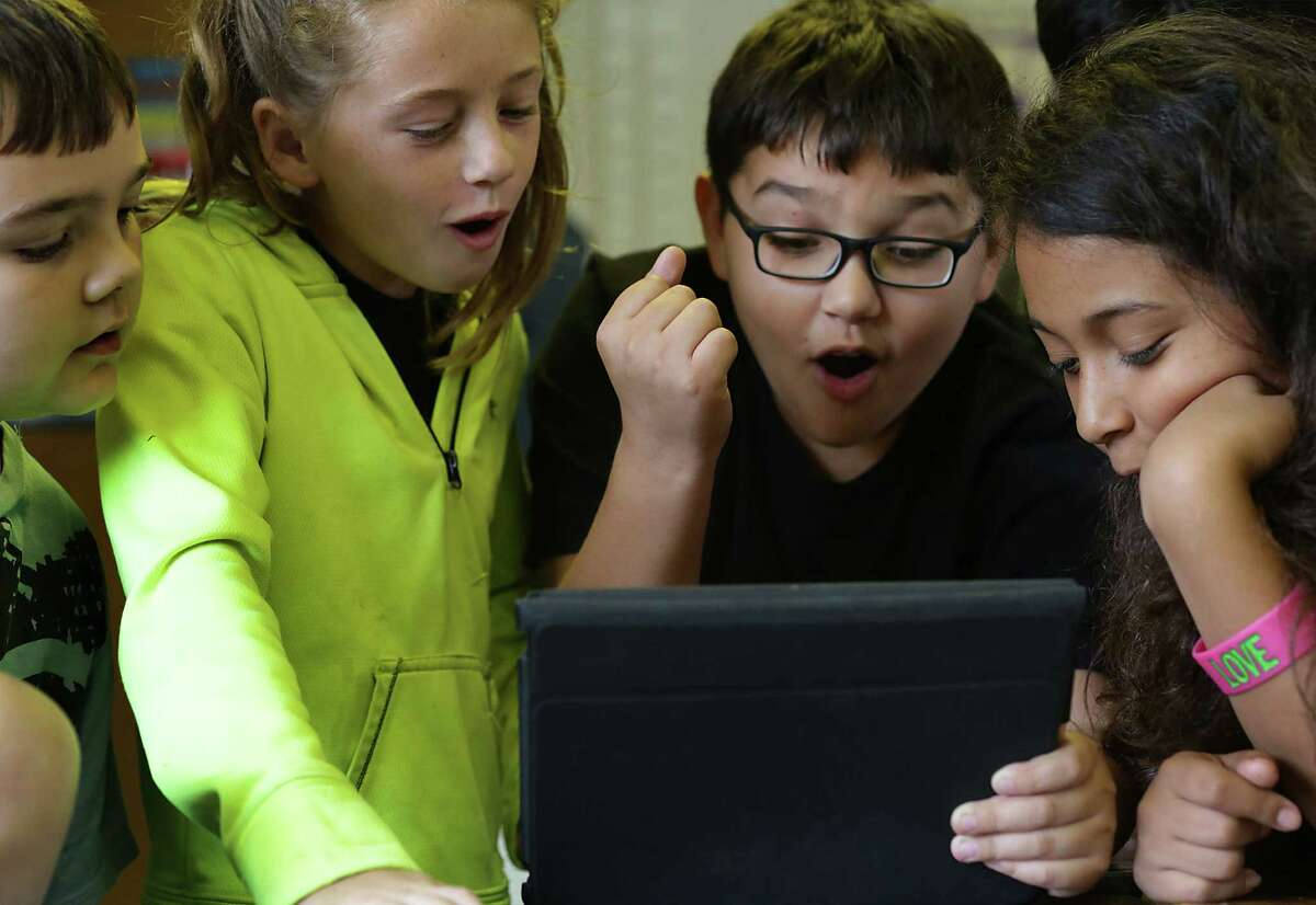 Students in Stephanie Waterhouse's fifth-grade class, Brendan Bell (from left), Bryley Coffel, Levi Perez and Kayasia Ponce, use a tablet and get a correct answer during math.