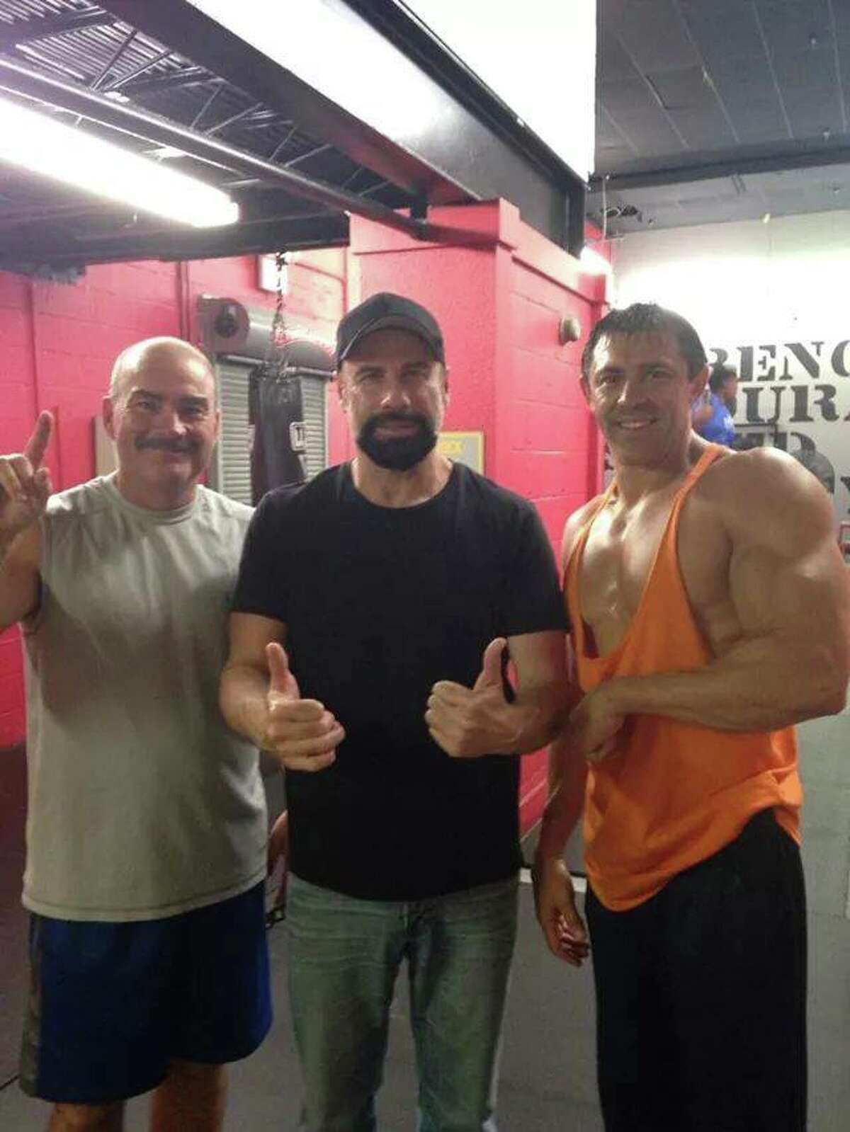 Actor John Travolta poses with fans at World Gym Fitness Center in Beaumont on Wednesday, September 24, 2014.