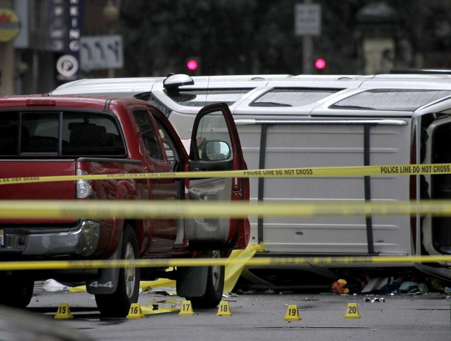 Evidence markers are placed in the street while police officers investigate after a high speed chase across the Golden Gate Bridge concluded with a crash involving at lease three vehicles at California and Battery streets in San Francisco, Calif. on Thursday, Sept. 25, 2014. Police officers reportedly shot and killed the suspect after he repeatedly refused orders to drop his weapon. Photo: Paul Chinn, The Chronicle