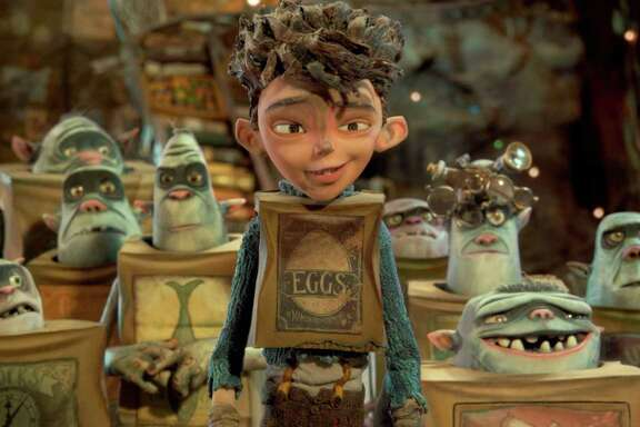 """Eggs, voiced by Isaac Hempstead Wright, is surrounded by his boxtroll friends in """"Boxtrolls."""""""