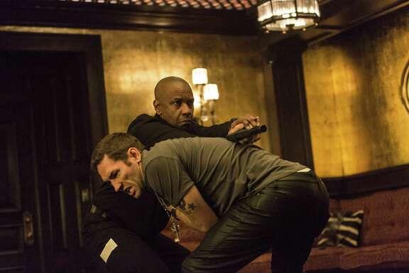 "Robert (Denzel Washington, holding gun) gets the drop on a bad guy (Nash Edgerton) in ""The Equalizer."""