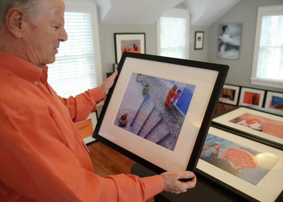 """Mike Harris shows a photograph from the Moroccan city of Chefchaoen, known as the blue city, in the studio of his home in Greenwich, Conn. Wednesday, Sept. 24, 2014.  Harris' photos from his recent two-month trip to Morocco will be on display at the Cos Cob Library in an exhibit titled """"Morocco Through the Lens"""" from October 1 through October 31 with an opening reception on Wednesday, Oct. 8 at 6 p.m. Photo: Tyler Sizemore / The News-Times"""