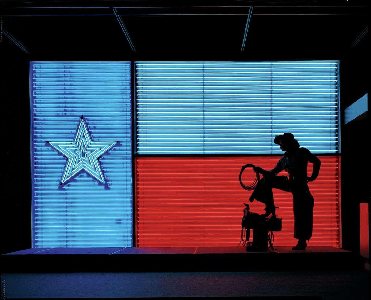 A cowboy silhouetted against a neon Texas flag.
