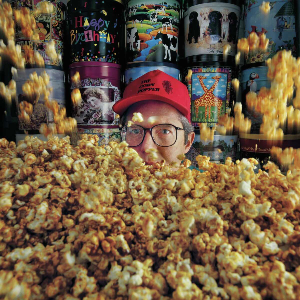 """J. Griffis Smith: """"When I arrived at the popcorn popper it was very sterile looking. I saw the decorative cans and the mound of popcorn and I used the cans to construct a wall behind the owner and had two of his employees and had them drop scoops of popcorn around him to get the illusion of popping."""""""