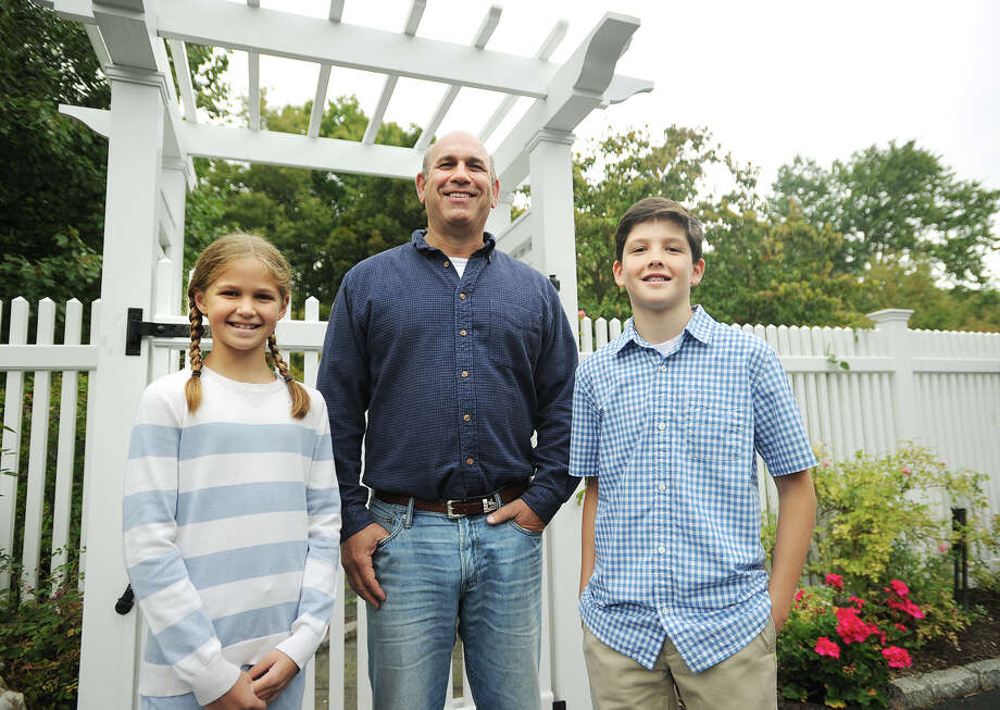 Riverside Fence owner Robert Kaye, of Redding, with clients Erik, 12, and Morgan Lebek, 10, in Wilton, Conn. on Thursday, September 25, 2014. Kaye's company has been named to the Inc. 500/500 list for a second consecutive year as one of the fastest growing privately held companies in the country. Photo: Brian A. Pounds / Connecticut Post