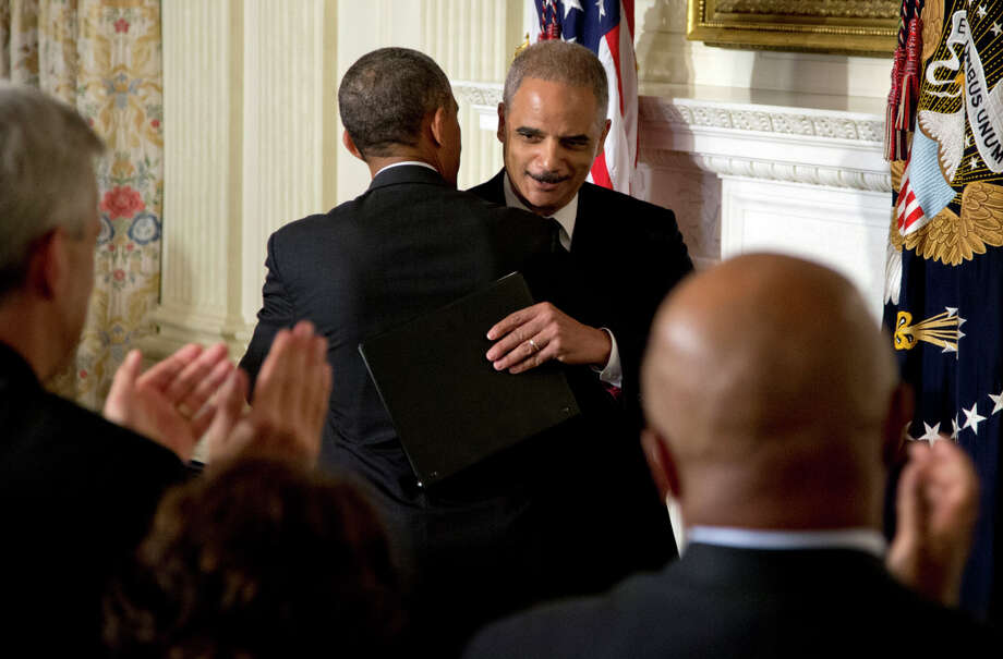 Attorney General Eric Holder embraces President Obama after announcing his resignation at the White House after more than five years in the job. Photo: Carolyn Kaster, STF / Associated Press / AP