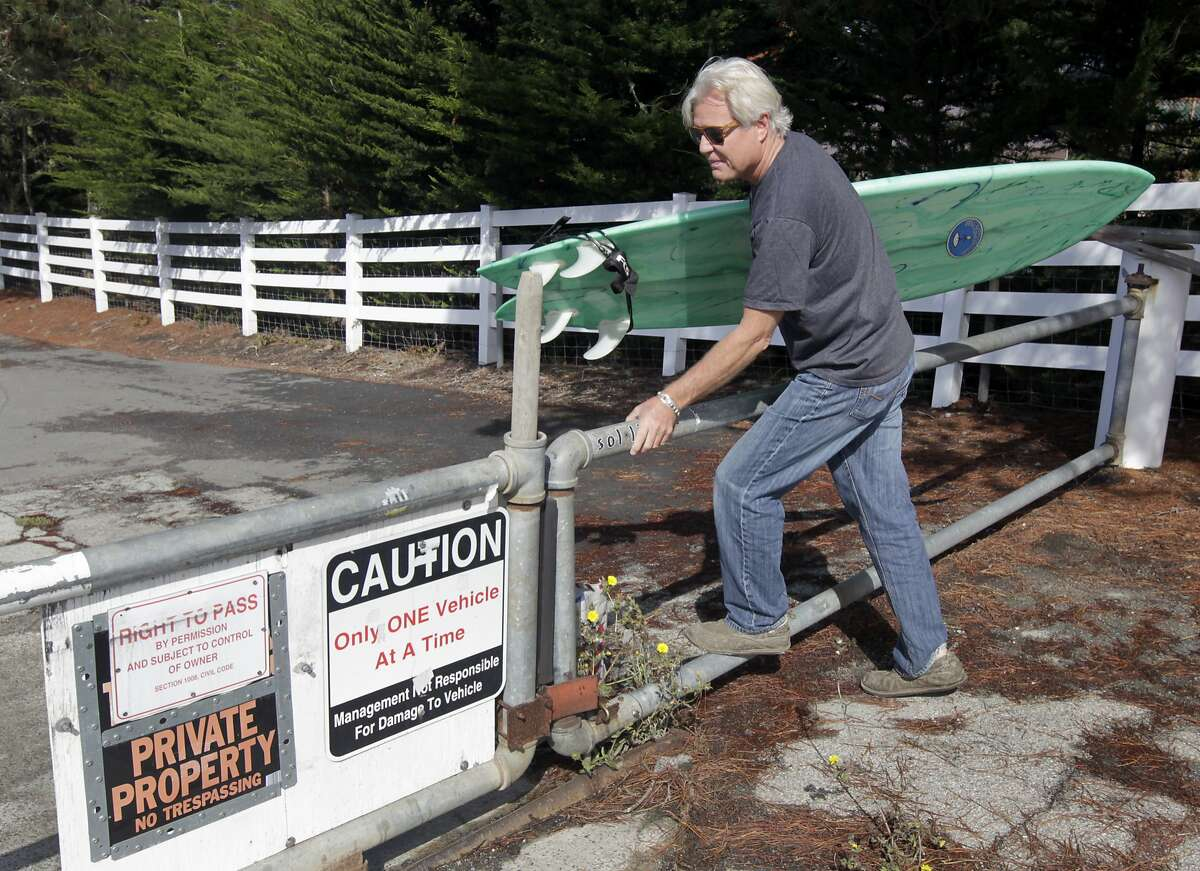 Mark Massara, one of the attorneys representing the Surfrider Foundation, hops a gate to Martin's Beach in Half Moon Bay, Calif. on Thursday, Sept. 25, 2014, which remained locked despite a judge's order to landowner Vinod Khosla to to open the private gate and allow public access to the beach.