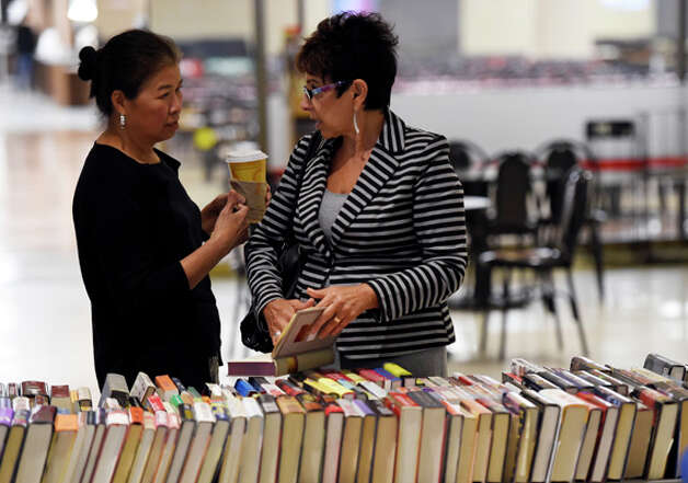 Chyongere Hsieh, let and Diane Ray discuss a potential book purchase during the book sale that benefits victims with AIDS Tuesday morning, Sept. 23, 2014, on the Empire State Plaza Concourse in Albany, N.Y. The event runs through Friday 10 a.m.- 4 p.m. (Skip Dickstein/Times Union) Photo: SKIP DICKSTEIN, ALBANY TIMES UNION / 00028709A