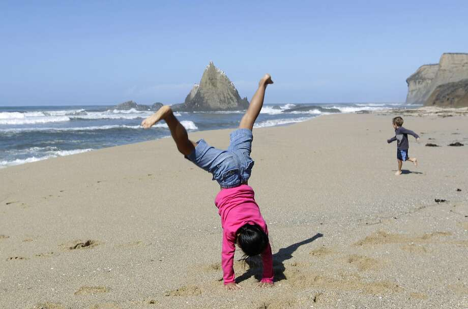 An Na Toth, 9, performs a cartwheel while visiting Martin's Beach with her brother Henry (right), 6,  in Half Moon Bay, Calif. on Thursday, Sept. 25, 2014, one day after a judge ordered landowner Vinod Khosla to unlock a private gate and allow public access to the beach. Public access has been spotty since then. Photo: Paul Chinn, The Chronicle