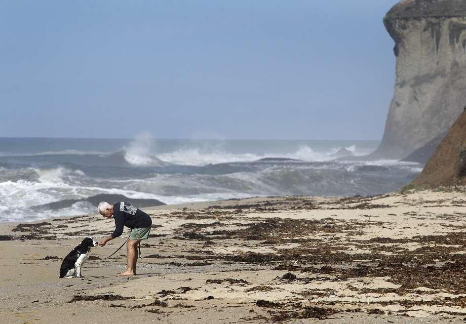 Tony Manzi and his dog Boo visit Martin's Beach in Half Moon Bay, Calif. on Thursday, Sept. 25, 2014, one day after a judge ordered landowner Vinod Khosla to unlock a private gate and allow public access to the beach. Khosla is challenging the judge's order to unlock the gate. Photo: Paul Chinn, The Chronicle