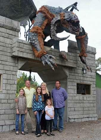 Owners David and Stacey Mulino with partner and head of operations Matt Dinon, right, along with their daughters, from left, Guiliana, 10, Amalia, 12, and Nadia, 5, stand under an animated monster at the the ticket booth for the Halloween season's Field of Horrors at Capital Combat Zone on Thursday, Sept. 25, 2014 in Brunswick, N.Y. (Lori Van Buren / Times Union) Photo: Lori Van Buren / 00028765A