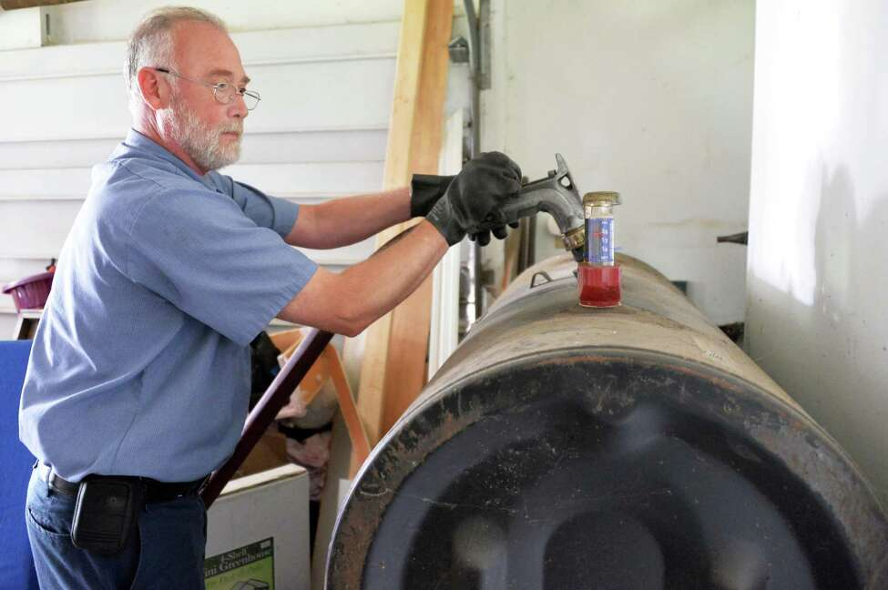 Heating oil delivery driver Glenn Hotaling of Family Danz Heating and Cooling delivers heating oil to a home Thursday Sept. 25, 2014, in Castleton, NY. (John Carl D'Annibale / Times Union)