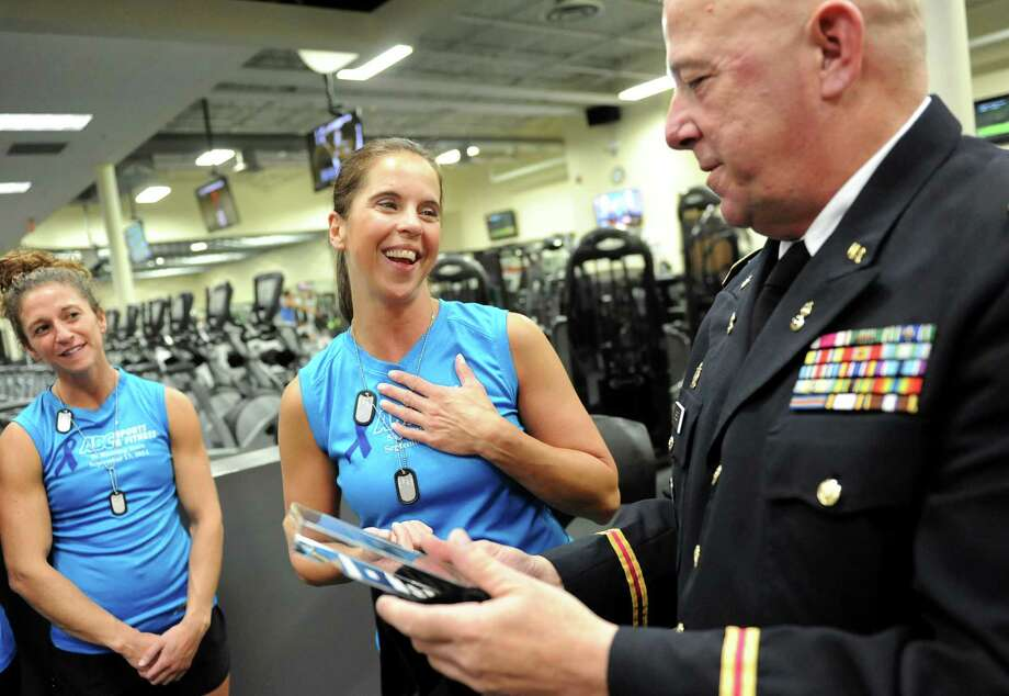"""Toni Howard, center, receives and award for outstanding leadership from CW3 Stephen Breen of the U.S. Army, right, on Thursday, Sept. 25, 2014, at ABC Sports and Fitness Center in Latham, N.Y. Lindsay Choppy, left, looks on. Howard started a fitness program, called """"Get Your Rear in Gear"""" to prepare runners for a 5K to raise funds for the Colon Cancer Coalition. (Cindy Schultz / Times Union) Photo: Cindy Schultz / 00028743A"""