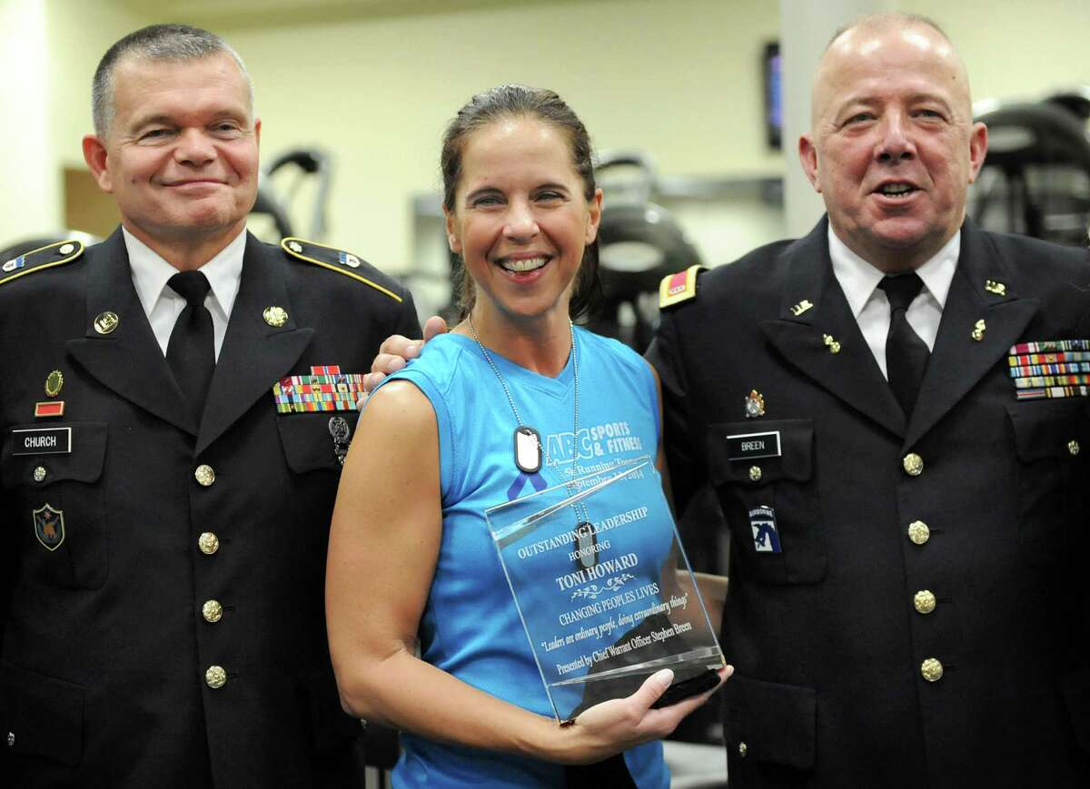 Toni Howard, center, receives an award for outstanding leadership from CSM Ken Church of the Army National Guard, left, and CW3 Stephen Breen of the U.S. Army on Thursday, Sept. 25, 2014, at ABC Sports and Fitness Center in Latham, N.Y. Howard started a fitness program, called