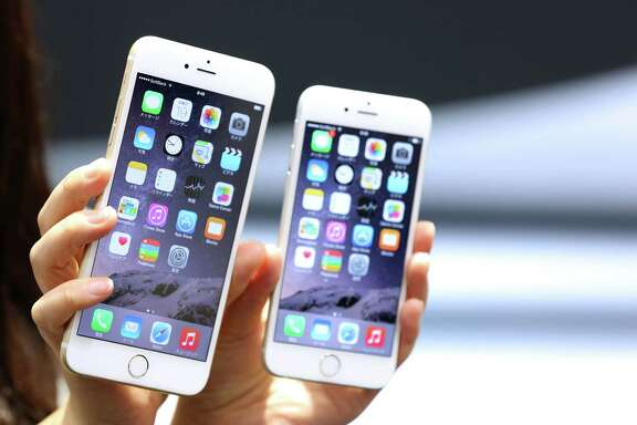 An Apple iPhone 6 Plus, left, and an iPhone 6 are displayed. A new mobile-software update, iOS 8.0.2, was released late Thursday.