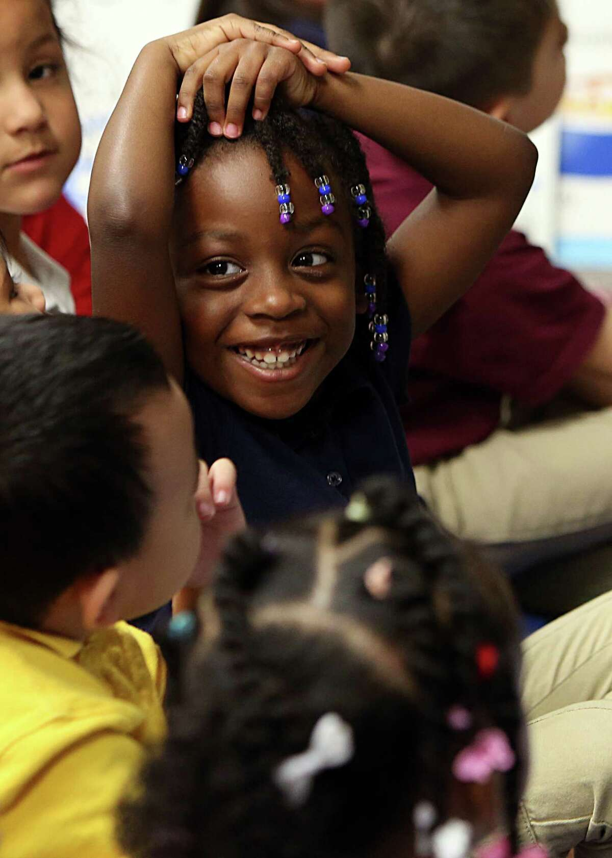 Trinidy Taylor, 4, smiles at teacher Lisa Joe during a morning pre-kindergarten lesson at Liestman Elementary School on Wednesday, Sept. 24, 2014, in Houston. A coalition of educators, business and civic leaders called Early Matters is pushing to expand high-quality, full-day pre-kindergarten for 4 year-olds in the greater Houston area. Alief ISD only offers half-day pre-kindergarten.