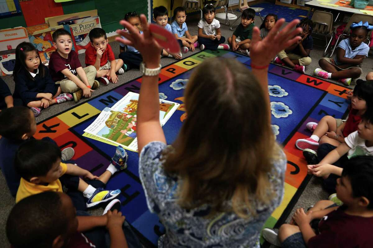 Pre-kindergarteners listen to teacher Lisa Joe as she tells a story during their morning lesson at Liestman Elementary School on Wednesday, Sept. 24, 2014, in Houston.