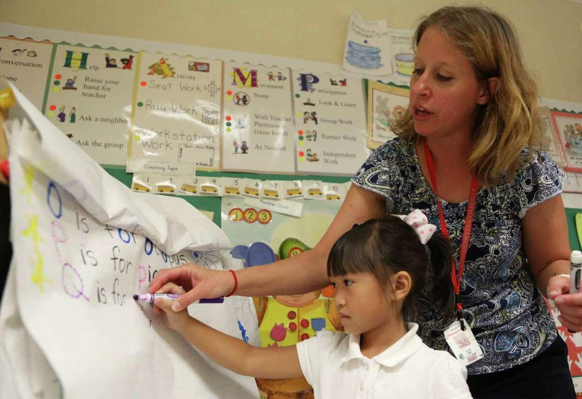 Teacher Lisa Joe helps pre-kindergartener Han Nguyen write during a morning lesson at Liestman Elementary School on Wednesday, Sept. 24, 2014, in Houston.