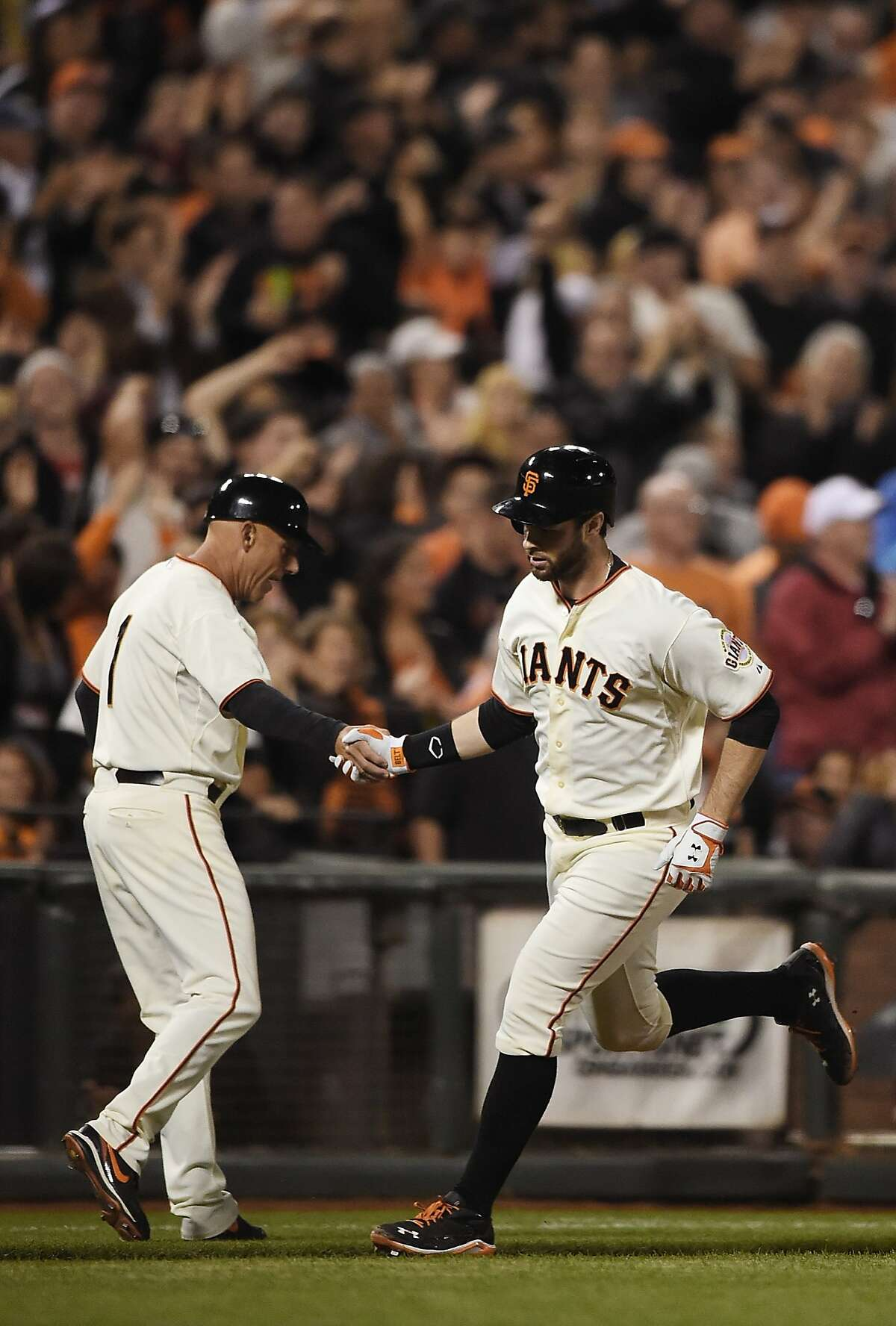 SAN FRANCISCO, CA - SEPTEMBER 25: Brandon Belt #9 of the San Francisco Giants is congratulated by third base coach Tim Flannery #1 after Belt hit a solo home run against the San Diego Padres in the bottom of the second inning at AT&T Park on September 25, 2014 in San Francisco, California. (Photo by Thearon W. Henderson/Getty Images)