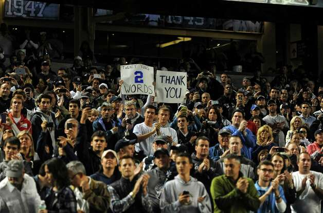 Fans hold signs honoring New York Yankees shortstop Derek Jeter during his final home game at Yankee Stadium, Sept. 25, 2014. Retiring after 20 seasons with the Yankees, Jeter inspired a cult of personality like few other athletes before. (Barton Silverman/The New York Times) ORG XMIT: XNYT204 Photo: BARTON SILVERMAN / NYTNS