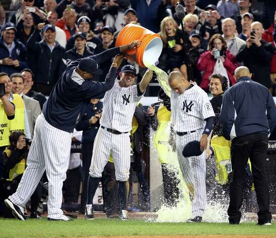 Teammates empty a bucket on Derek Jeter of the New York Yankees after his final game at home in Yankee Stadium in the Bronx, New York, Thursday night, Sept. 25, 2014. The Yankees beat Baltimore, 3-2.  (Michelle V. Agins/The New York Times)  ORG XMIT: NYT6 Photo: MICHELLE V. AGINS / STAFF