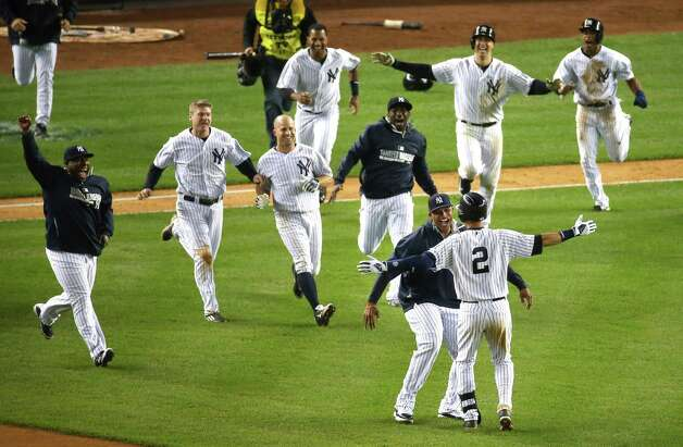 Derek Jeter of the New York Yankees is greeted by teammates after driving in the game-winning run on his final game at Yankee Stadium in the Bronx, New York, Thursday night, Sept. 25, 2014. (Chang W. Lee/The New York Times)  ORG XMIT: NYT8 Photo: Chang W. Lee / Chang W. Lee/The New York Times
